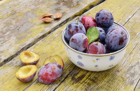 Ripe plums in metal bowl placed on shabby wooden table photo