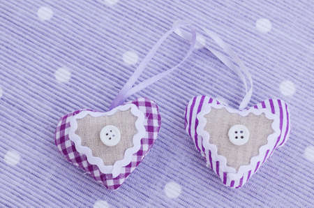 Two decorative lavender aroma hearts placed on table napkin of tender lavender color photo