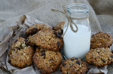 coffeetime: Oatmeal cookies and bottle of milk on canvas background