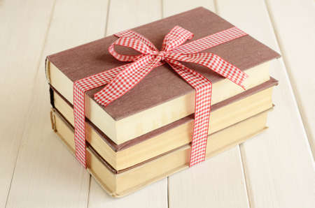 Pile of books bounded up in red-and-white ribbon on white wooden background photo