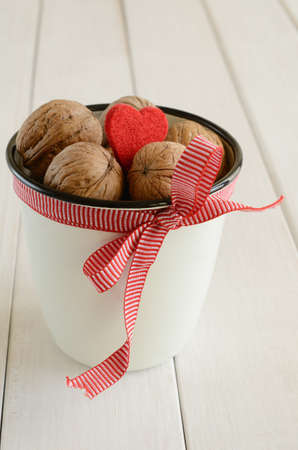 bounded: Walnuts in white cup bounded up in red-and-whote ribbon and bow with small red heart, on white wooden background Stock Photo