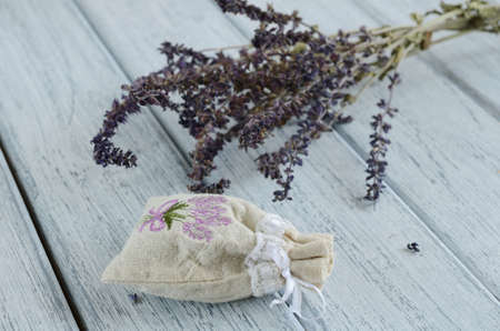 Lavender aroma bag and bunch dried of lavender on shabby wooden background photo