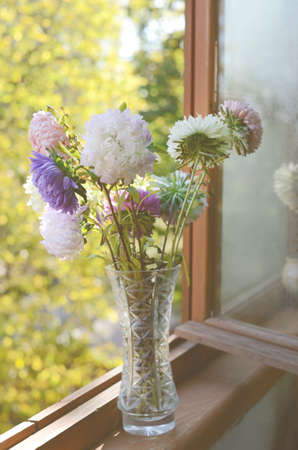 Autumn golden-daisy bunch in crystal vase on old wooden window-sill photo
