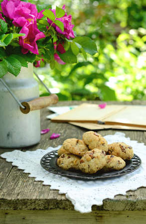 Sill life with walnut cookies on lace doily, dog rose bunch in vintage milk can and notebook on rusted garden table photo