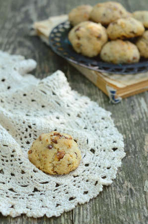 Sigle walnut cookie over vintage lace doily on rusted wooden table photo