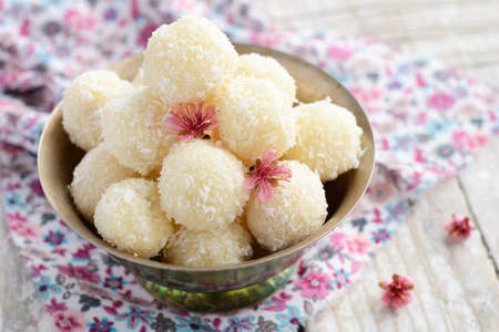 metal ball: Homemade coconut balls decorated with little pink flowers in metal bowl, wooden background