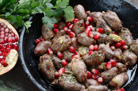 Fried chicken hearts with garlic, coriander, spicy and pomegranate in Georgian style on iron pan photo