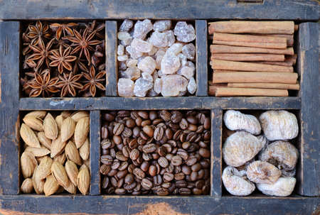Mix of coffee beans, almond, brown sugar, figs and spices in old rusted wooden box photo