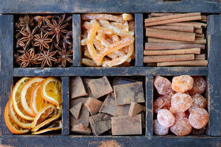 Dark chocolate, kumquats, dried orange slices, cinnamon, candied peels and star anise in old wooden crate photo