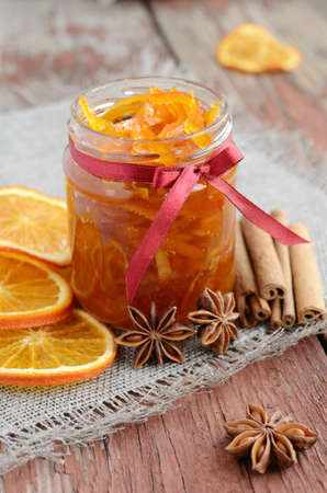 Homemade candied peels orange confiture in glass jar with spices - cinnamon and anise star on rusted wooden background photo