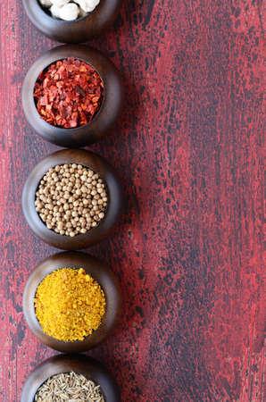 indian spices: Set van houten schalen met Indische kruiden - witte kardemom, chili, koriander, gele kruidige noten mix en komijn, op geroeste houten achtergrond