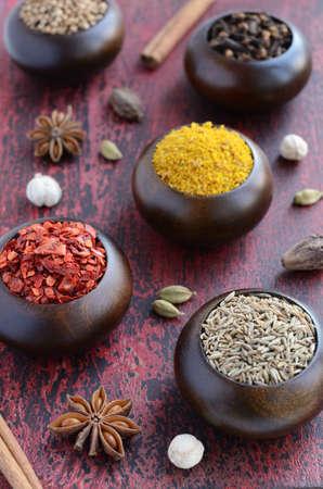 indian spices: Set van Indiase kruiden - komijn, chili, gele moer kruidige mix, koriander, witte, zwarte en groene kardemom, nootmuskaat, kaneel, steranijs en kruidnagel op verroeste houten achtergrond