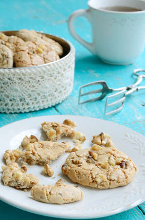 Homemade almond cookies with walnut on white plate  and cup of tea placed on blue shabby wooden background photo