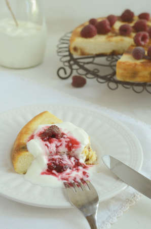a jar stand: Breakfast with homemade cottage cheese baked pudding with raisins topped with sour cream and fresh raspberry sauce on light background