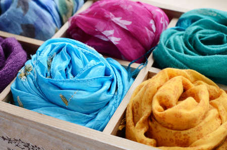 clothes organizer: Wooden box with different colorful scarfs Stock Photo