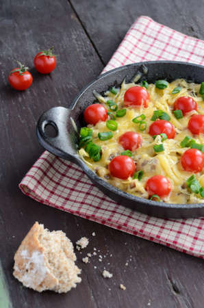 topped: Homemade baked minced meat with cheese and cherry tomatoes topped with chopped green onion in cast-iron cooking pan, on wooden background Stock Photo