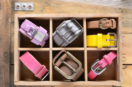 Set of colorful leather belts in wooden divider crate on military rusted wooden background