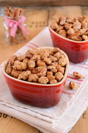 sugared: Roasted sugared almond with cinnamon in heart shaped red bowls on wooden background