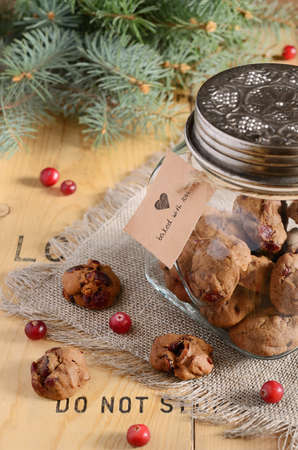 Christmas decoration with butter chocolate cookies, fresh cranberry and fir tree branches on wooden background photo