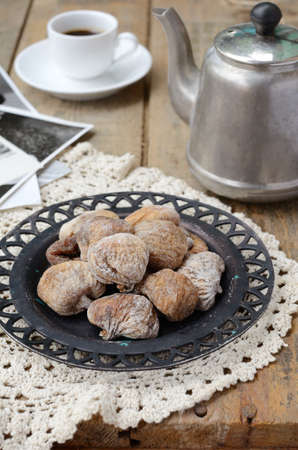 Still life with dried figs on lace doily, coffee pot, cup of coffee and vintage cards on wooden background photo