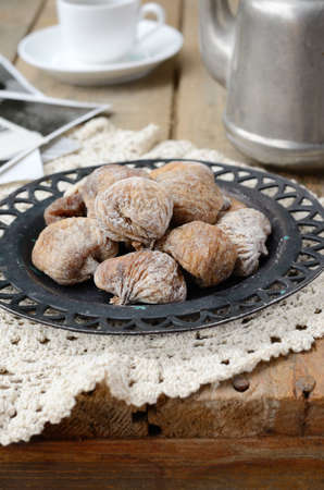 Still life with sun dried figs on metal plate, vintage coffee pot, coffee cup and retro shots on wooden background photo