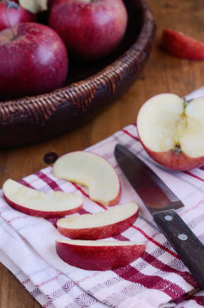 Cutting ripe apple with  knife on red and white country towel on wooden table photo