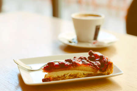 Piece of wild strawberry cake with cream and cup of espresso on the table in cafe photo