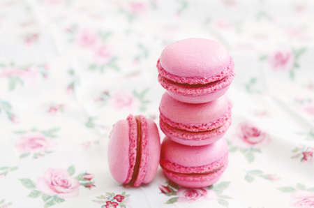 Stack of tender pink cherry macaron on floral background photo