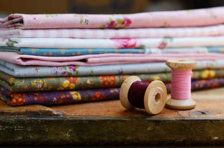 Vintage wooden thread spools and floral pattern fabric set on rusted wooden table with selective focus on spools photo