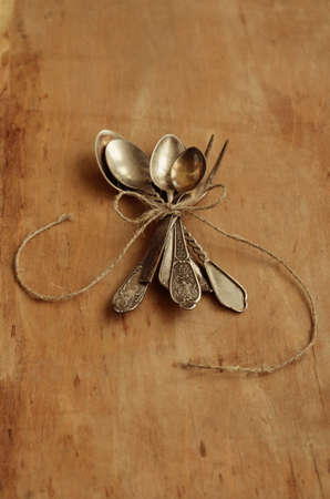 Bunch of vintage teaspoons and lemon fork tied up with jute rope and decorated with bow over aged background photo