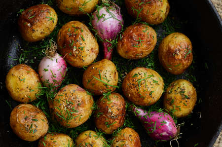 baked potato: Whole fried yound potato and young onion topped with spices and chopped dill in cast iron pan