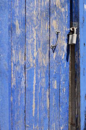 wicket door: Deep blue rusty wicket door with metal handle and lock with selective focus on lock
