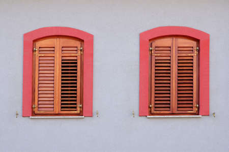 jalousie: Two red windows with wooden jalousie on white wall
