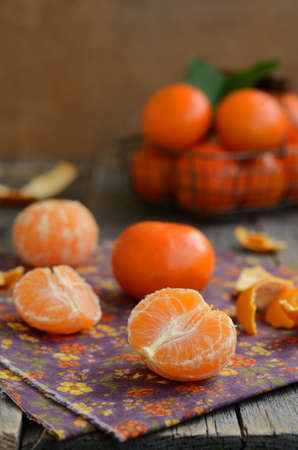 orange peel clove: Cloves of tangerines and wire basket full of ripe fruits against wooden background with copyspace Stock Photo
