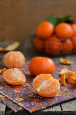 orange peel clove: Spicchi di mandarini e di cestello pieno di frutti maturi contro sfondo di legno con copyspace Archivio Fotografico