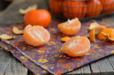 orange peel clove: Ripe and juicy tangerine cloves over bright violet table napkin Stock Photo