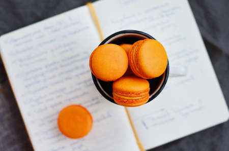 open diary: Orange macaroon upon open diary with notes