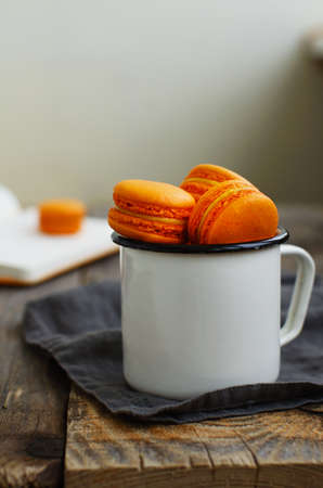tradional: White metal cup full of orange colored  and passion fruit French macarons on wooden table Stock Photo