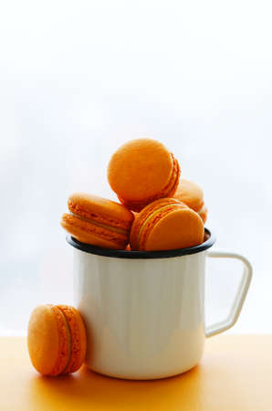 tradional: Mango and passion fruit macarons of orange color in enamel cup Stock Photo