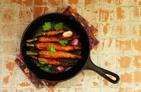 cast iron: Whole baked young carrot with garlic and rosemary topped with coriander leaves in cast iron pan