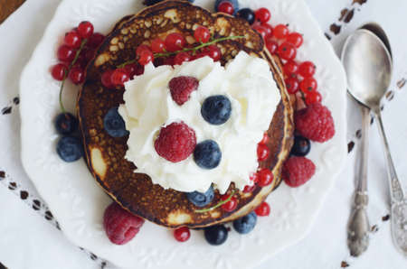 bilberry: Homemade thin pancakes with whipped cream and fresh berries - raspberry, black and red currant and bilberry