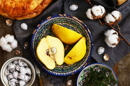 pits: Quince in pattern ceramic bowl, oriental flatbread, salty apricot pits, baking stamp and cotton flowers Stock Photo
