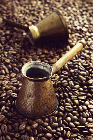 cezve: Vintage copper coffee cezve for turkish coffee in coffee beans Stock Photo