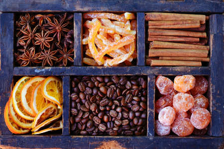 sugared: Set of coffee beans, sugared oranges and kumquats, cinnamon, candied peels and star anise in rustic wooden display