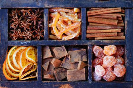 bitter orange: Bitter chocolate, kumquats, dried orange slices, cinnamon, candied peels and anise stars in wooden display Stock Photo
