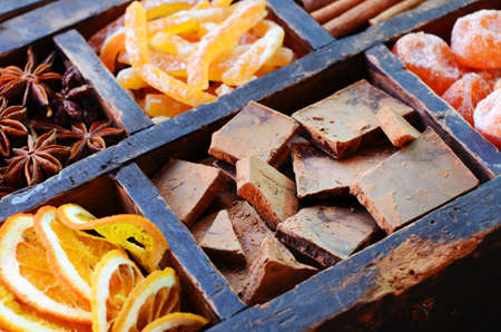 sugared: Set of dark chocolate, sugared oranges and kumquats, cinnamon, anise stars in wooden box Stock Photo
