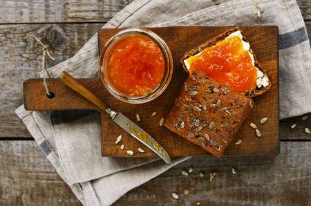 marillenmarmelade: Roggenbrot und Aprikosenmarmelade Sandwich auf Schneidebrett
