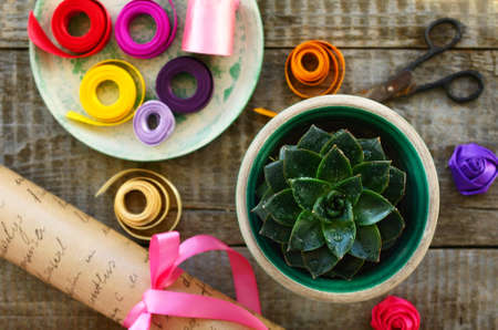 Table in flower shop - stone rose cactus, wrapping paper roll, set of colorful ribbons, bow and decor, vintage scissors photo