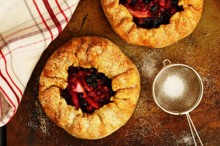 Just baked crusty galette with apples and berries topping with sugar on baking sheet