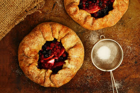 open topped: Just baked homemade open pies or galette with apples and berry mix, topped with sugar on baking paper